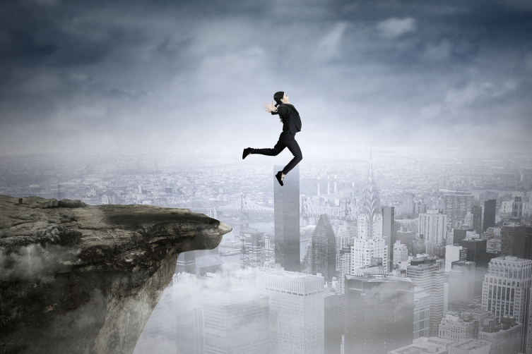 Businesswoman Jumping Against City Background